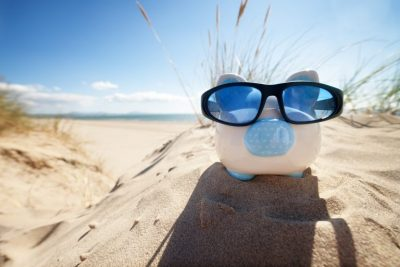 Piggy bank on the beach, taking a holiday from pension contributions