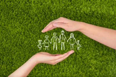 A drawn stick family protected by two hands, life insurance keeping family safe.